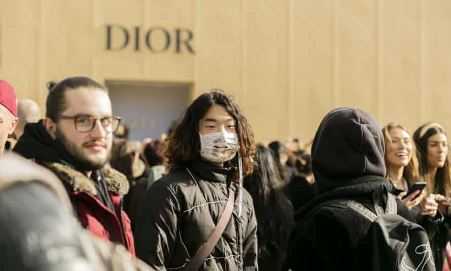 A man in a torn face mask queues to see the Christian Dior collection.