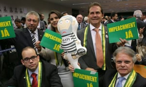 Opposition deputies show posters that read in Portuguese 'impeachment now' and an inflatable doll in the likeness of former president Luiz Inacio Lula da Silva in prison garb, during impeachment talks in Brasilia on Wednesday.