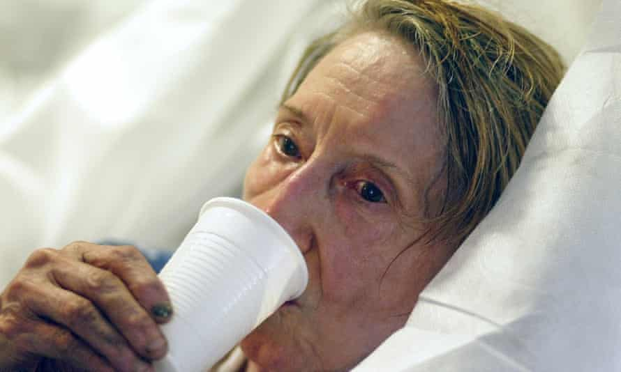 An elderly woman who wished to remain unidentified drinks after she was brought by firefighters to the Saint Antoine hospital in Paris during a 2003 heatwave.
