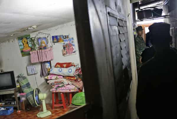 Thai soldiers search workers' living quarters during a raid on a shrimp shed in Samut Sakhon, Thailand