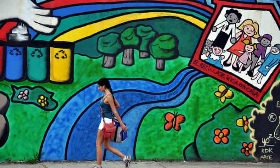 A Costa Rican girl walks past a mural in favor of recycling and the environment on a street of San Jose,