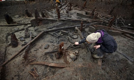 An archaeologist works on the site destroyed by a fire 3,000 years ago at Must farm quarry in Cambridgeshire.