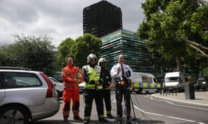 Met police commander Stuart Cundy makes a statement to the media against the backdrop of the remains of Grenfell Tower.