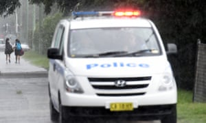 Students depart a Sydney high school as police patrol the grounds following a threat on Monday.