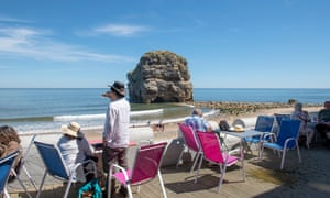 Marsden Rock with beach and people in chairs