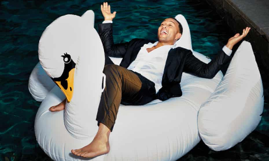 John Legend lying back, arms open, on an inflatable swan