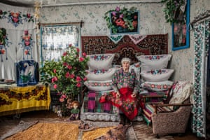 Markevich Volha Fedarauna poses at the house (Belarus, 2018). A widowed woman sits at her home in Belarus. Surrounded by flowers, embroidery and dolls, she dries grain on her carpeted floor