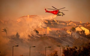A helicopter makes a water drop to help fight the Saddleridge fire north of Los Angeles.
