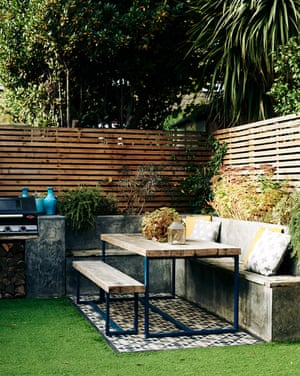The garden serves as an outdoor room in summer, complete with artificial grass, bench seating and a dining table found on eBay.