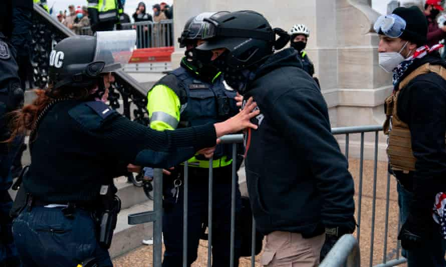 A protester confronts police officers as Trump supporters riot outside the US Capitol on 6 January.