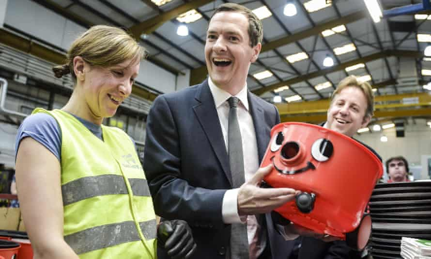George Osborne shares a joke and admires his handy-work after putting together the face onto a 'Henry' vaccum in Chard, Somerset.