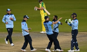 England's wicket keeper Jos Buttler celebrates with bowler Adil Rashid as England win.