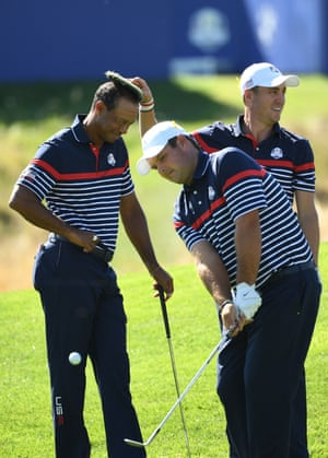 Tiger Woods smiles as Justin Thomas places a tuft of turf on his head as Patrick Reed plays a shot.