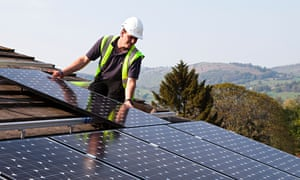 An engineer fits solar panels to a house in Wales