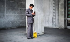 A man carrying a large jug of vegetable oil checks his mobile phone before getting on the metro, in Pyongyang, North Korea.