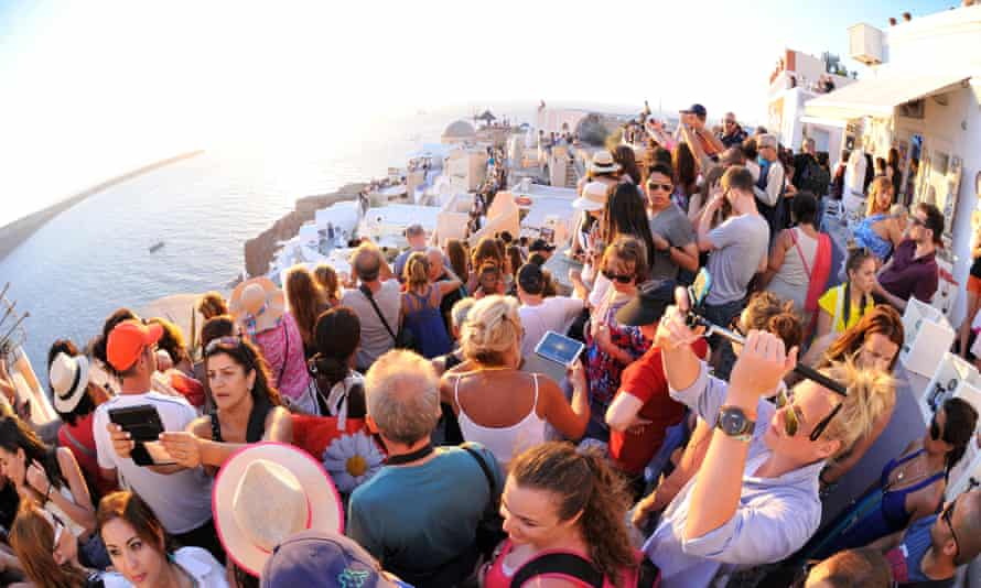 Crowd puller … tourists jostling for a sunset shot in Oia, Santorini.