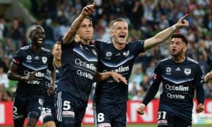 Mark Milligan celebrates his match-winning penalty in the Melbourne derby with Besart Berisha.
