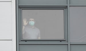 A person wearing a mask stands at a window of the accommodation block where British nationals flown back from China are being quarantined.