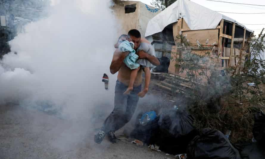 People flee teargas fired by riot police after a fire at Moria camp on Lesbos