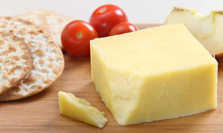 Wedge of cheddar cheese on board with crackers and cherry tomatoes
