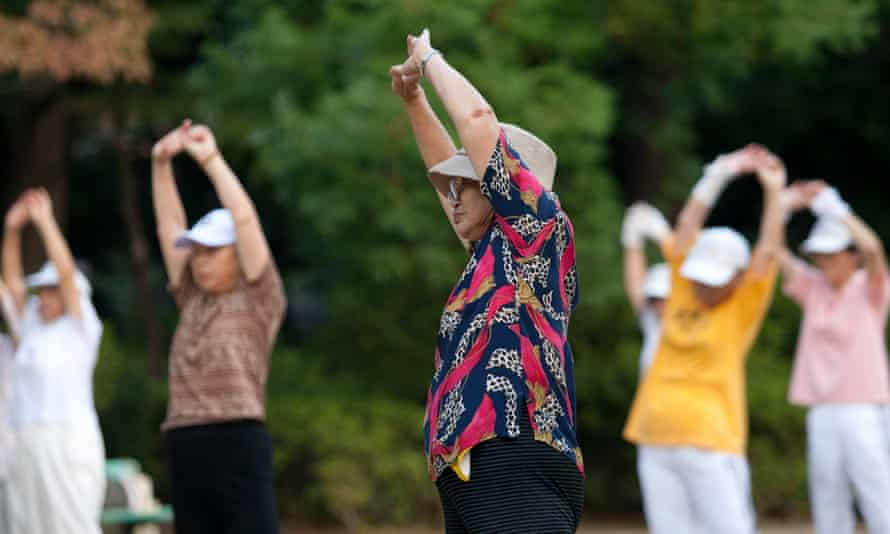 People exercise to an NHK radio calisthenics broadcast at a park in Tokyo.