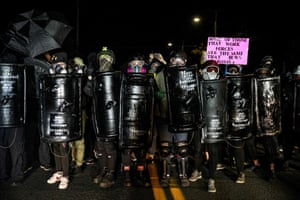 Protestors wearing gas masks and carrying homemade shields take part in the 100th day and night of protests against racism and police brutality in Portland.
