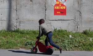 A boy rides a toy scooter past an election campaign poster for the Economic Freedom Fighters in Cape Town.