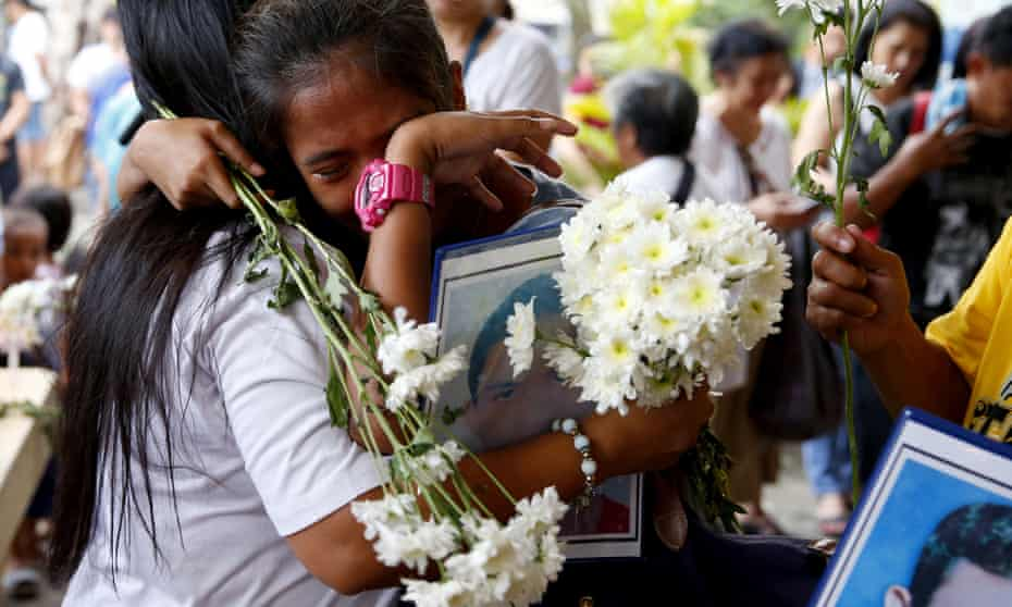 Relatives of victims in Philippine president Rodrigo Duterte's 'war on drugs' comfort each other at a church in Quezon city in 2019