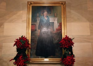 A portrait of former first lady Laura Bush, surrounded by holiday arrangements.