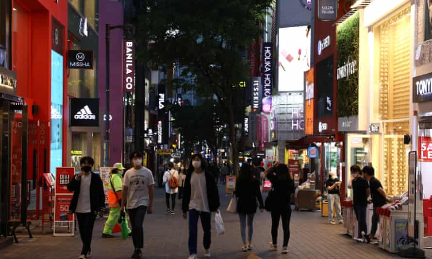 People walk along a street in Seoul. South Korea has won widespread praise for its 'track and trace' model of containing the pandemic