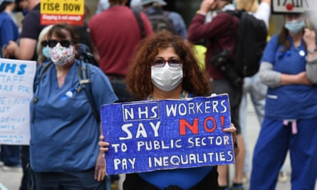 A woman in a face mask at a demonstration  holding up a sign saying 'NHS workers say no to public sector pay inequaliies'