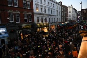People enjoy drinks outside on Old Compton Street, central London, on the first Friday evening after pubs in England were allowed to reopen to serve customers outside.