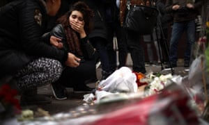 A woman reacts after placing flowers near the scene of the Bataclan theatre attack.