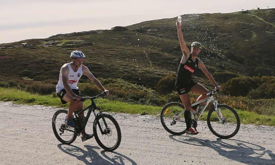 Two men on mountain bikes, one spraying water over himself
