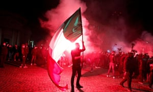 A demonstrator holds an Italian flag during a protest over restrictions put in place to curb coronavirus cases