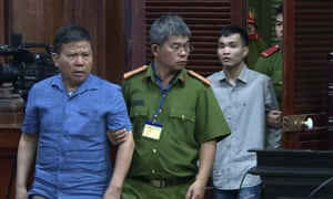 Sydney man Chau Van Kham, left, is escorted into a court room in Vietnam