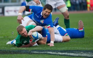 Ireland's Keith Earls scores a try under the challenge of Italy's Alessandro Zanni