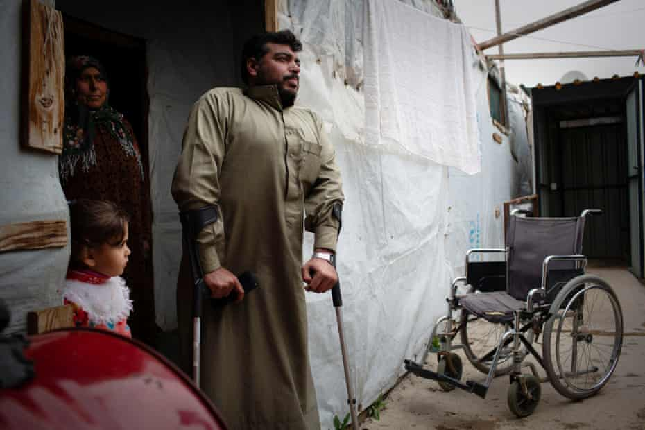 Lemeh, 34, who suffered from polio and was injured in the war, stands in the door of his family's shelter with his mother and niece, Zahlé, Lebanon, 23 March 2021
