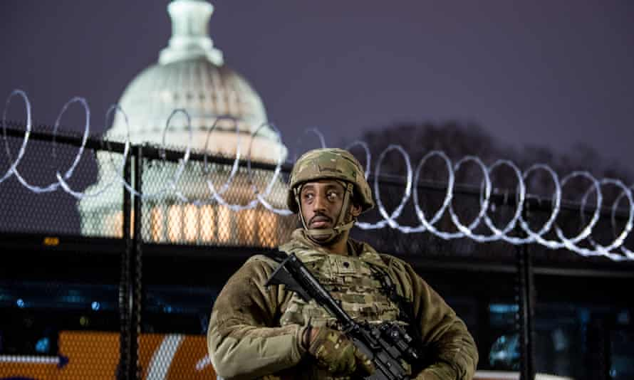 A member of the Virginia national guard stands outside razor wire fencing surrounding the US Capitol.