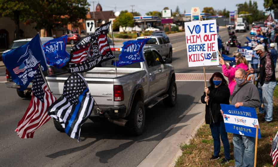 Supporters of Donald Trump drive by a group supporting Joe Biden in Minnesota.