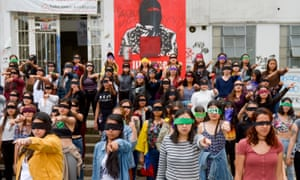 Women's rights activists wearing black bands in front of their eyes, protest against gender violence at the National University in Bogota on 29 November 2019.