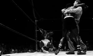 Knocked unconscious by a lethal barrage of blows, the defeated champion Paret sags on the ropes as referee Goldstein keeps a tight hold on Emile Griffith.