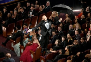 Keegan-Michael Key, one of several guests giving awards in the absence of a host, descends to the floor with an umbrella