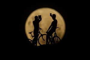 Cyclists take photos of the super moon in Lancelin, Australia