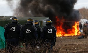 French riot police stand by a burning shelter during the demolition of part of the Jungle migrant camp.