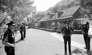 Police officers stand guard outside the Los Angeles home of Sharon Tate following her murder in August 1969.