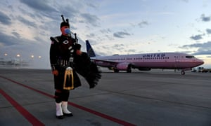 Aurora, Colorado firefighter Tom Johnson stands at attention as the United Airlines flight carrying the body of retired paramedic Paul Cary arrives at Denver International Airport on Sunday.