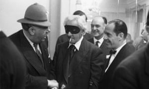 Hannen Swaffer, with mask and cigarette, at a party in December 1955.
