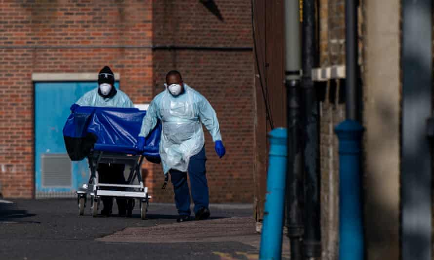 BAME hospital workers in full PPE transporting a blue trolley