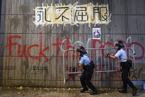 Police remove barricades under a poster displayed on a wall with remnants of thrown eggs and graffiti sprayed by protesters outside the police headquarters in Hong Kong early on June 22, 2019.